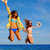 Young girls on holiday jumping with hats. Stock Photo