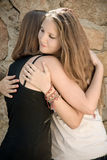 Young Girls Hug. Two Young Girls Hug with stone wall at the background Stock Photography