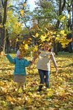 Young girls jump on yellow leaves in autumn park. Happy childhood stock photo