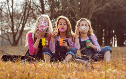 Young girls kids sisters blowing bubbles with soap in a farm fie Stock Images