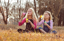Young girls kids sisters blowing bubbles with soap in a farm fie Stock Image