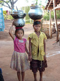 Young girls learn how to carry water Royalty Free Stock Photos