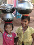 Young girls learn how to carry water Stock Photo