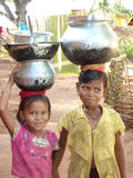 Young girls learn how to carry water in pots Royalty Free Stock Photography