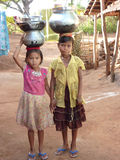 Young girls learn how to carry water in pots Royalty Free Stock Photos