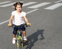 Young girls learn to ride a bike Stock Images