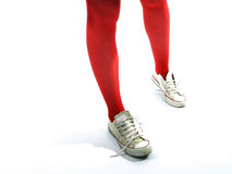 Young girls legs in red tights and old sneakers. Against a white background Stock Image