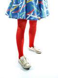 Young girls legs in red tights trainers and colour. Ful dress against a white background Royalty Free Stock Photography