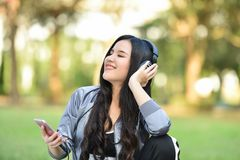 Listen to music. Young girls listen to music smartphones in relax exercise Woman during fitness the park garden Royalty Free Stock Image