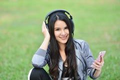 Listen to music smartphones. Young girls listen to music smartphones in relax Royalty Free Stock Photos