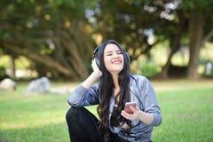 Listen to music smartphones. Young girls listen to music smartphones in relax exercise Woman during fitness the park garden stock image