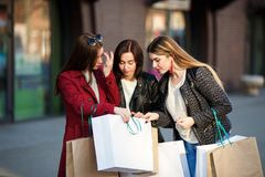 Young girls look into paper bag near shopping mall. Young beautiful girls look into paper bag near shopping mall. Shopping, purchase, leisure, people concept Royalty Free Stock Photography
