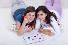 Young girls in love writing in a diary Stock Photos