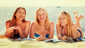 Young girls lying on beach. Three young smiling girls in swimwear lying together on beach. Focus on all persons Stock Photography