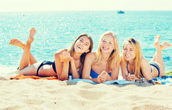 Young girls lying on beach. Three young smiling girls in swimwear lying together on a beach. Focus on all persons Royalty Free Stock Photo