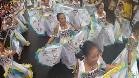 Young girls in ornate butterfly costume dance along the street, a festival to honor a patron saint. San Pablo City, Laguna, Philippines - January 13, 2014: Young stock footage