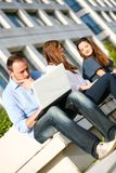 Young girls outdoors and man with laptop Stock Photography