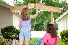 Young girls paintng lemonade stand Royalty Free Stock Photos