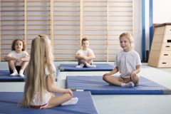 Young girls in PE class. Happy young girls sitting across from each other on blue exercising mats with their legs crossed during PE classes in the primary school Royalty Free Stock Photos