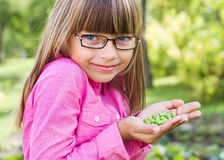 Young girls and peas Stock Images