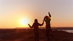 Young girls with phone listening to music on headphones against the sunset, girls with headphones dancing to music. stock video