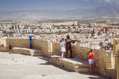 Young girls are photographed on the background of the fortress of Santa Barbara, Alicante, Spain. ALICANTE, SPAIN - SEPTEMBER 9, 2014: young girls are Royalty Free Stock Photography
