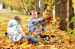 Young girls play outdoors in the autumn season royalty free stock photo