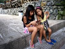Young girls play a video game on a smartphone while sitting on a set of steps. royalty free stock image