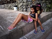 Young girls play a video game on a smartphone while sitting on a set of steps. royalty free stock photography
