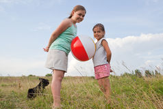 Young girls playing with a ball outdoors Stock Photos