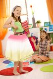 Young girls playing at home fitting dresses Stock Photos