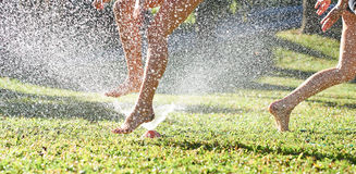 Young girls playing jumping in a garden water lawn sprinkler Royalty Free Stock Image