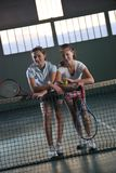 Young girls playing tennis game indoor Royalty Free Stock Photos