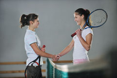 Young girls playing tennis game indoor Stock Photo