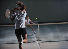 Young girls playing tennis game indoor Stock Images