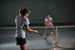 Young girls playing tennis game indoor Royalty Free Stock Images