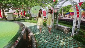 Young Girls Pose at Decorative Bench by Pond in Vietnam. NHA TRANG, KHANH HOA/VIETNAM - JANUARY 26 2017: Vietnamese young girls in white dresses pose near stock footage