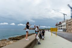 HAVANA, CUBA - OCTOBER 21, 2017: Young Girls Posing in Malecon Avenue, Havana, Cuba. Young Girls Posing in Malecon Avenue, Havana, Cuba Royalty Free Stock Images