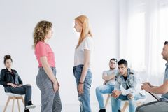 Young girls during psychotherapy. Young girls facing each other during psychotherapy with rebellious teenagers in white office royalty free stock photos
