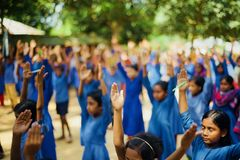 Young girls raising their hands in an assembly royalty free stock image