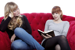Young girls read a book on red sofa Stock Photos