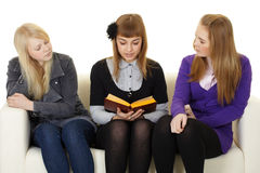 Young girls read fiction on couch Stock Photography