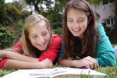 Young girls reading a book. Young girls investigating reading a book in their garden Royalty Free Stock Image