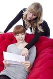 Young girls on red sofa point on letter Stock Image