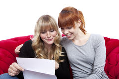 Young girls on red sofa reading a letter Royalty Free Stock Photo
