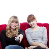 Young girls on red sofa with remote control Royalty Free Stock Photos