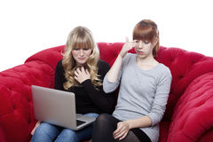 Young girls on red sofa are shocked Royalty Free Stock Photo