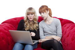 Young girls on red sofa showing on laptop Royalty Free Stock Photos