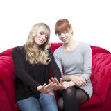 Young girls on red sofa wondering fingernails Stock Images