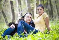 Young girls resting in forest. A view of two young, pretty girls, resting in a clearing or opening in the forest on a spring day Stock Photo